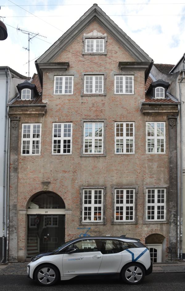Farvefoto af bygningen Åbenra 25 - foran holder en elbil