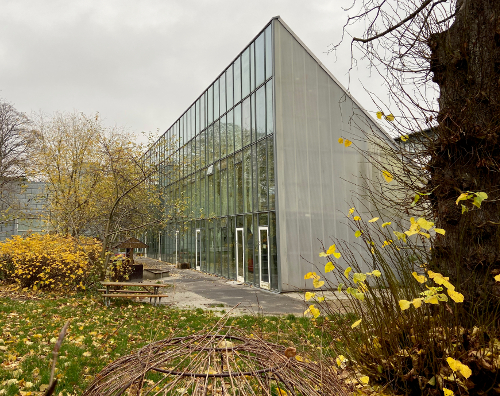 En moderne bygning med glasfacade og bagudskrånende tag