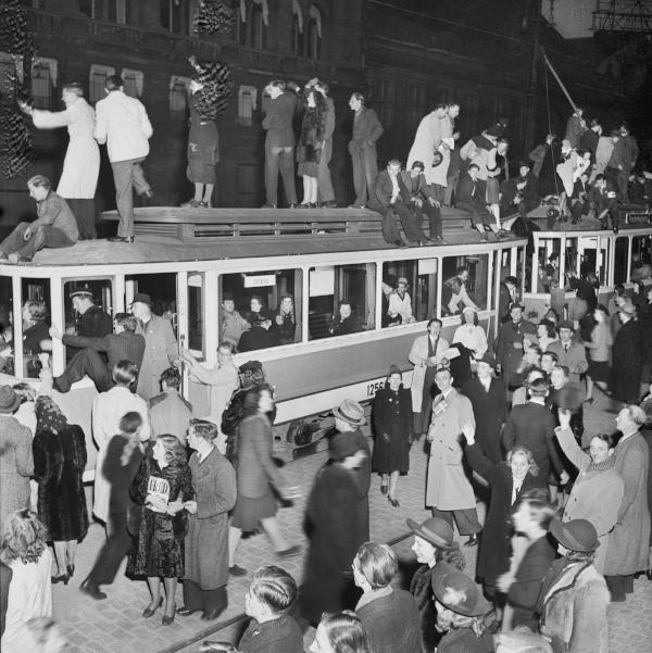 Festlig folkemængde ovenpå og ved siden af sporvogn