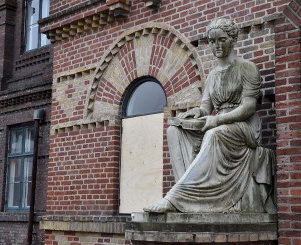 Skulptur af blind pige der med fingrene læser i en bog