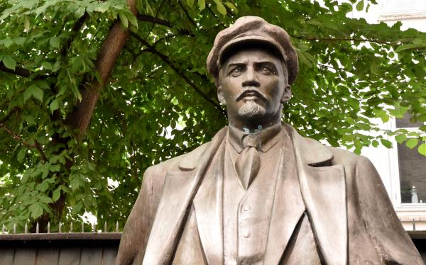 Statue af Lenin foran grøn træ, nederst i billedet ses kanten af et stakit
