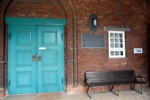 Mindetavle på rødstensmur mellem en grøn dør og et vindue