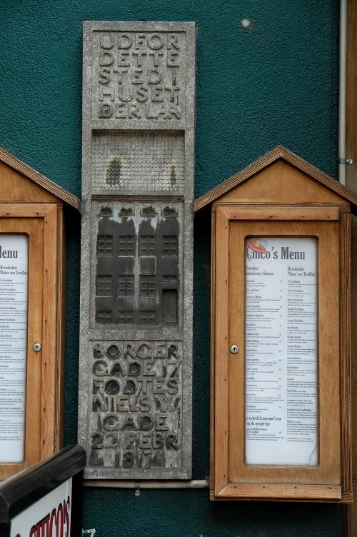 Mindetavle på grøn mur, med relief af forsvundet bygning