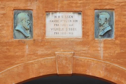 Mindetavle mellem to portrætter i profil