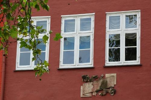 Mindetavle på rød mur - under to vinduer. Mindetavlen er udsmykket med to engle