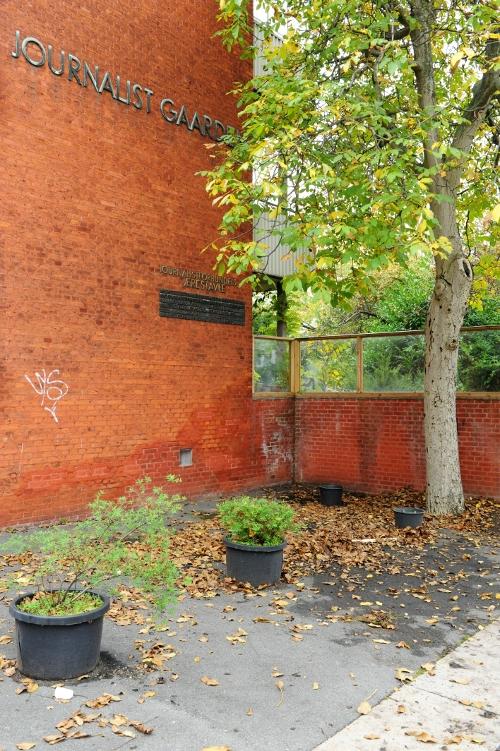 Mindetavle på murstensmur bag et træ