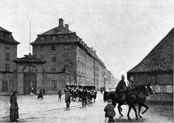 Sølvgadens Kaserne i sort hvid. Gardens afløste vagt paa hjemmarch. Tilhøjre de gamle længer ved de kongelige driverier.