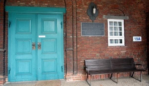 Mindetavle på en rød murstensnur, til venstre for en grønlig dør