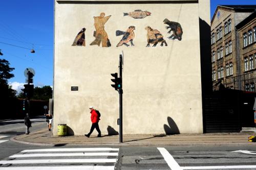 Mindetavle på endegavl af hus, ovenover set kunstværk med figur af dyr