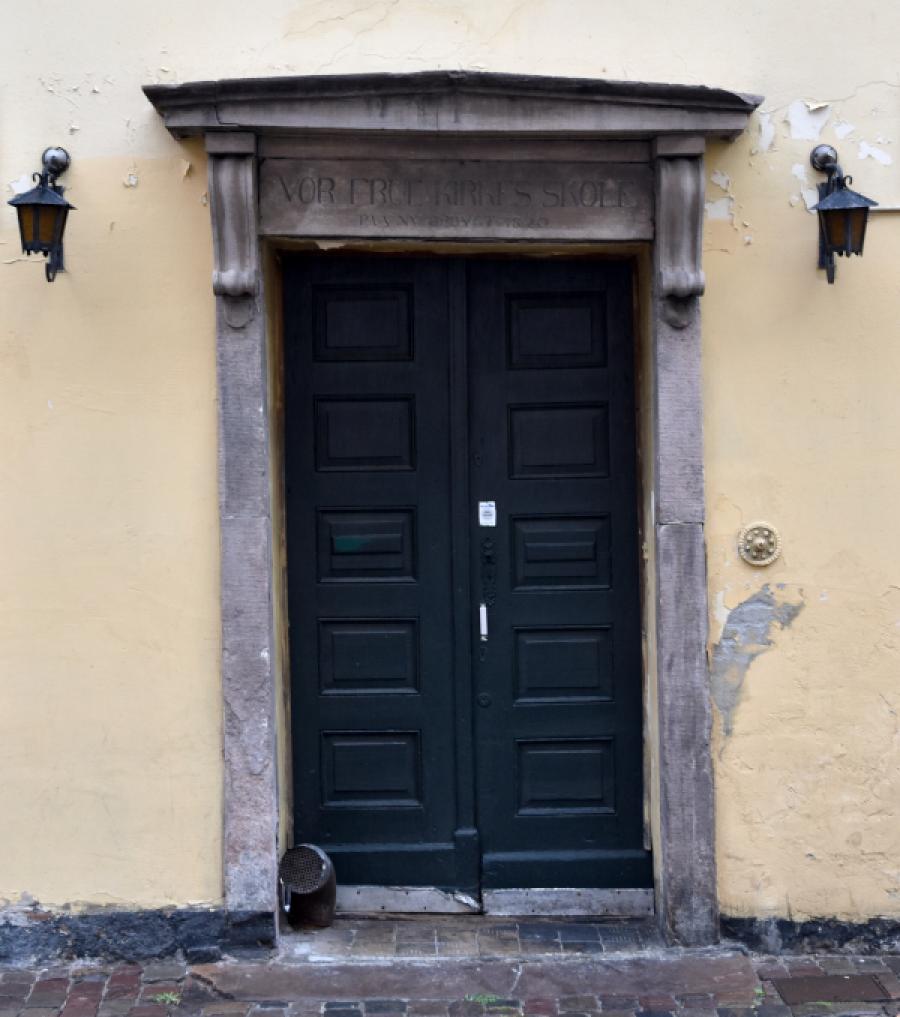 """Dør med portal og teksten """"VOR FRUE KIRKES SKOLE / PAA NY OPBYGT 1820"""""""