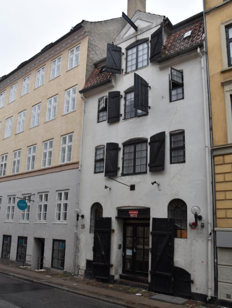 Hus med tre fag og med vinduesskodder til midterste række af vinduer