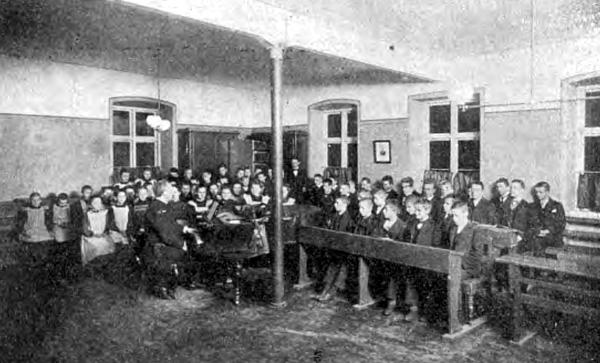 Undervisningslokale med børn på rad og række. Drenge og piger hvert for sig.